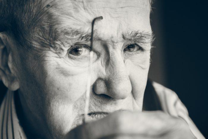 Ein alter Mann in Nahaufnahme schaut nachdenklich in die Kamera.