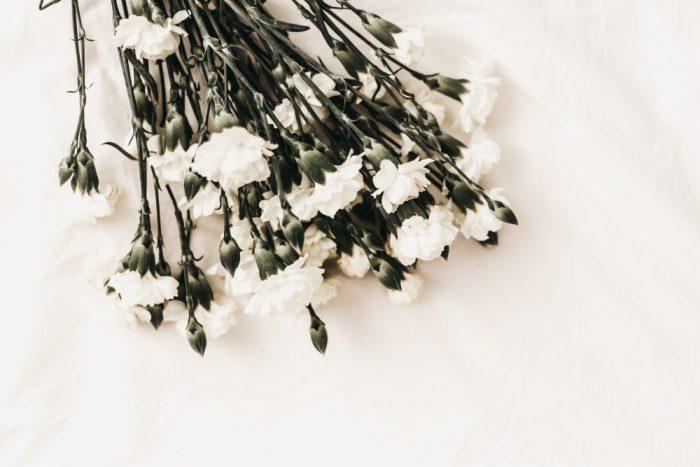 Ein Strauß weißer Nelken auf weißem Tuch als Symbol für Beerdigung und die Zeit danach.